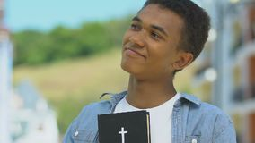 Teen african-american boy embracing Bible, religious vocation to clergy, priest