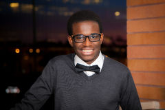 Teen African American Boy. A teenage african american boy wearing a bowtie smiles for the camera with the late afternoon sunlight reflecting in the mirrored Royalty Free Stock Photography