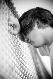 Teen against fence. Teen depressed against chain-link fence in black and white. Shallow focus stock image