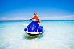 Teenager on water scooter. Teen age boy water skiing. Teen age boy skiing on water scooter. Young man on personal watercraft in tropical sea. Active summer Royalty Free Stock Photography
