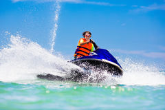 Teenager on water scooter. Teen age boy water skiing. Teen age boy skiing on water scooter. Young man on personal watercraft in tropical sea. Active summer Royalty Free Stock Photos