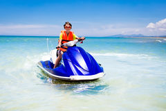Teenager on water scooter. Teen age boy water skiing. Teen age boy skiing on water scooter. Young man on personal watercraft in tropical sea. Active summer Stock Photography
