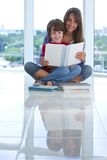 Teen age sister holding her little brother on her lap, holding a book and looking at camera Royalty Free Stock Photos