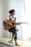 Teen ager playing folk guitar Stock Photos