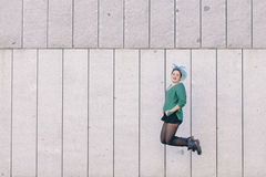 Teen androgynous woman jumping with blue dyed hair and wearing a stock photo