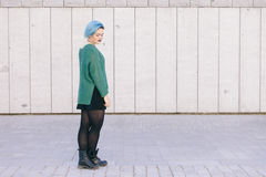 Teen androgynous woman on a sad expression with blue dyed hair i. Solated on the street wearing a blue sweater Royalty Free Stock Image