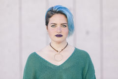 Teen androgynous woman with sad expression and blue dyed hair is. Olated on the street wearing a nose piercing Stock Photography