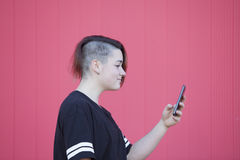 Teen androgynous young woman connecting to internet on a pink backgrou Stock Photo