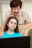 Teen Annoyed by Mom. Teen girl annoyed by her aunt watching her work on the computer Royalty Free Stock Photo