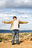 Teen with arms wide open. Teen male standing in the wind on the edge of a cliff, arms wide open royalty free stock image
