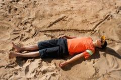 Teen artist. Artistic teenager sunbathing next to his beach cartoon Royalty Free Stock Photo