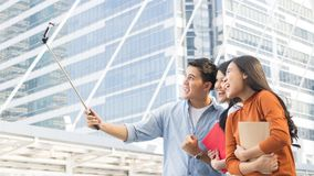 Teen asia people use smart phone to selfie, self-portrait photog. Raphy shoot, held in the hand and supported by a selfie stick Royalty Free Stock Image