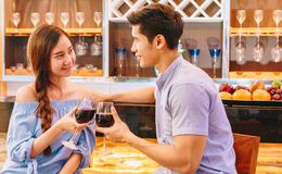 Couple in the bar. Teen Asian couple drinking wine in front of the bar to drink in their home to celebrate Valentine`s day royalty free stock photo