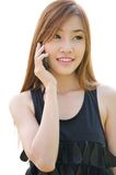 Teen Asian girl using cell phone. Closeup portrait of a cute Asian girl talking on mobile phone against white background Royalty Free Stock Photos