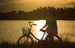 Teen asian woman sit at retro vintage bicycle near the lake at sunset moment. silhouette bicycle at the sunset with grass field. Big mountain and sunset stock photography