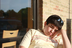 Teen, Asleep. Teen boy fell asleep while leaning on his hand outside in a chair Royalty Free Stock Image