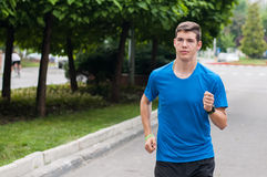 Teen athlete training by running on street Stock Photos