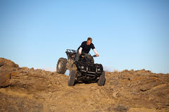 Teen on ATV quad in the hills. Teen on ATV quad - four wheeler going down sandstone hills Royalty Free Stock Images