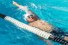 Teen backstroke swimmer in action. Close up action shot of teen boy swimming backstroke in swimming pool Royalty Free Stock Image