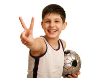 Teen with a ball showing a victory sign Royalty Free Stock Images