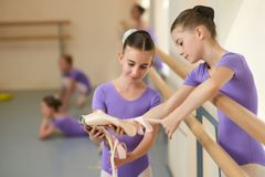 Teen ballerina showing her slippers to friend. Little ballerinas having a rest. Beautiful ballet dancers having communication during break. Friendship and Stock Photos