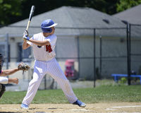 Teen baseball batter. Teenage baseball player in the batter's box. The batter is ready to swing and is wearing a white uniform with red pinstripes royalty free stock photos