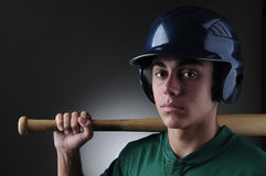 Teen Baseball Player with Bat. Closeup of a Teenage baseball player holding a bat on his shoulder. Horizontal format with a light to dark gray background Royalty Free Stock Images