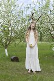 Teen beautiful blonde girl wearing white dress with deer horns o stock photo