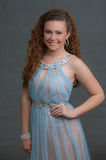 Teen beauty in blue dress showing smile expression. Half body view of pageant girl facing forward in elegant sheer dress Royalty Free Stock Photos