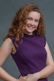 Teen beauty in purple dress grinning to camera right Royalty Free Stock Photography
