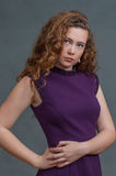 Teen beauty in purple dress poised to the right Stock Photos