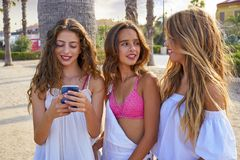 Teen best friends girls play with smartphone. Teen best friends girls group playing with smartphone in palm trees beach Stock Images