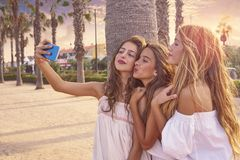 Teen best friends girls group shooting selfie. Photo smartphone in palm trees beach filtered image Royalty Free Stock Photography