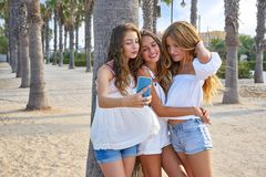 Teen best friends girls group shooting selfie. Photo smartphone in palm trees beach Stock Images