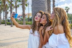 Teen best friends girls group shooting selfie. Photo smartphone in palm trees beach Stock Photography