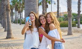 Teen best friends girls group shooting selfie. Photo smartphone in palm trees beach Stock Photo