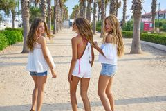Teen best friends girls walking in palm trees. Teen best friends girls group walking happy in a palm trees beach area Stock Image