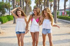 Teen best friends girls walking in palm trees. Teen best friends girls group walking happy in a palm trees beach area Stock Image