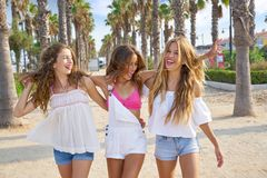 Teen best friends girls walking in palm trees. Teen best friends girls group walking happy in a palm trees beach area Stock Images