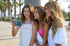 Teen best friends girls play with smartphone. Teen best friends girls group playing with smartphone in palm trees beach Royalty Free Stock Photo