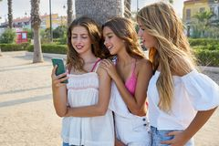 Teen best friends girls play with smartphone. Teen best friends girls group playing with smartphone in palm trees beach Royalty Free Stock Image