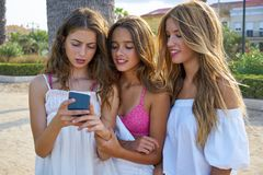 Teen best friends girls play with smartphone. Teen best friends girls group playing with smartphone in palm trees beach Royalty Free Stock Photos