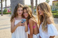 Teen best friends girls play with smartphone. Teen best friends girls group playing with smartphone in palm trees beach Stock Photography