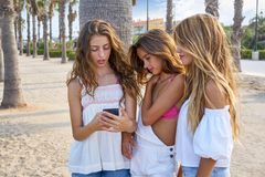 Teen best friends girls play with smartphone. Teen best friends girls group playing with smartphone in palm trees beach Royalty Free Stock Images