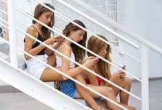 Teen best friends girls in a row with smartphone Stock Photos