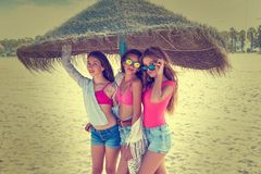 Teen best friends girls under thatch umbrella. Having fun on a beach Royalty Free Stock Photography