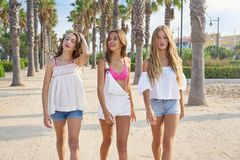 Teen best friends girls walking in palm trees. Teen best friends girls group walking happy in a palm trees beach area Royalty Free Stock Image