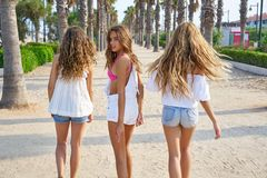 Teen best friends girls walking in palm trees. Teen best friends girls group walking happy in a palm trees beach area Stock Photos