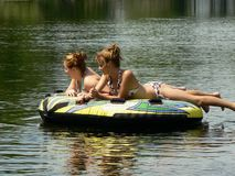 Teen Best Friends Reflecting on the River. My teenage daughter and her friend relaxing on a tube (and posing) on a lazy ride down the river behind our boat on a Stock Photo