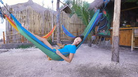 Teen with black hair lying on a blue hammock next to the bar, slowly falling asleep, thinking about the day. Teenage girl with short curly black hair, tired lies stock footage